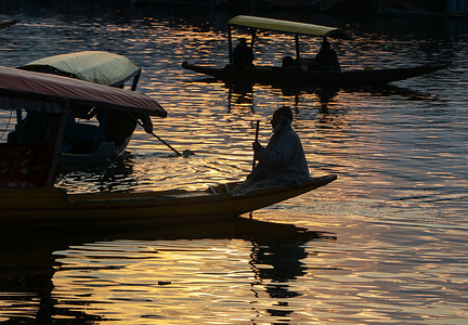 SRINAGAR, INDIA, 25 FEBRUARY 2021 - Silhouette of Kashmiri boatman rows his boat on the waters of Dal lake during sunset in Srinagar, Jammu and Kashmir.
