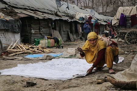 A woman among the rag pickers stitching a sheet used for their livelihood