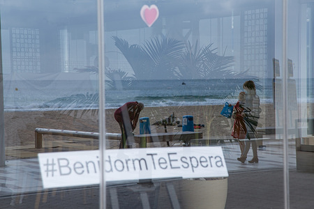 In the window of a hotel on the Benidorm promenade closed due to the lack of tourists you can read a message that says: Benidorm awaits you.