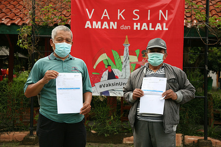 Two elderly people showed their Covid-19 Vaccine card after receiving an injection of the Corona Vaccine produced by Biofarma which was named the Covid-19 Vaccine with EUA number 2102907543A1 in the first mass Covid-19 vaccination program, at High School in Lubang Buaya, East Jakarta, Wednesday (3/3/2021). The elderly group is a priority target in the first stage of the advanced Covid-19 vaccination in Indonesia.