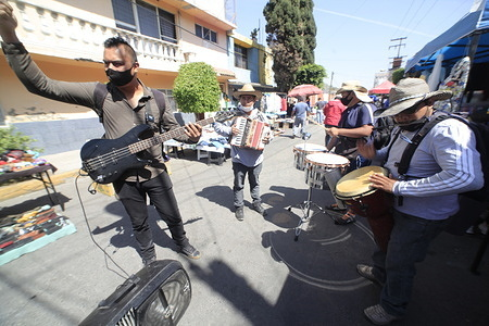 STATE OF MEXICO, MEXICO - MARCH 5: Musicians  in a market of Nezahualcoyotl City at east of the State of Mexico. People go out into the streets without respecting social distance and safety protocols, while the authorities have allowed the resume of commercial activities on March 5, 2021 in State of Mexico, Mexico