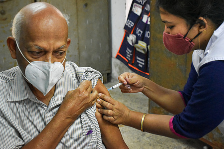 An old person receives a dose of Covishield, a covid vaccine during vaccination drive for people above 60 years of age and those who are 45 or more and suffering from certain medical conditions at Kolkata Municipality medical centre.