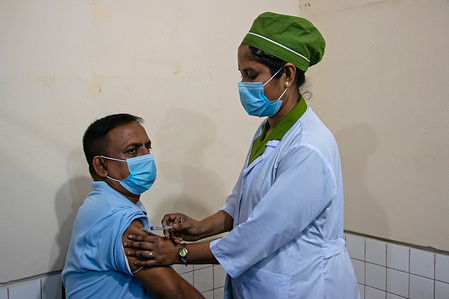 A man receives a dose of COVISHIELD, a coronavirus disease (COVID-19) vaccine, during a vaccination drive for people above 45 years of age and those who are suffering from certain medical conditions at a government hospital in Bangladesh.