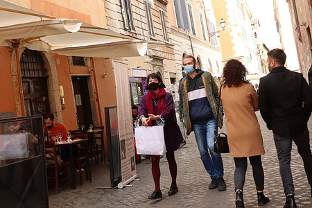 People stroll through the streets of the city center, wearing protective masks, during the covid-19 pandemic.