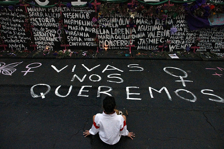 A woman, takes part during a performance of Feminist groups, to write names of victims of femicide and place flowers in protest against gender violence, as part of the protests of International Women's Day at the National Palace.