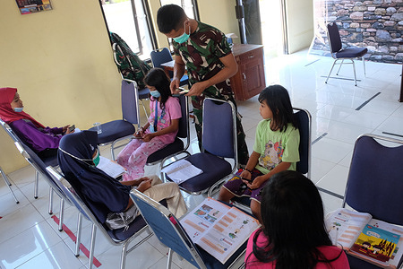 Students accompanied by members of the TNI study online at the 110th TNI Manunggal Build Village (TMMD) Post in Parepare City, South Sulawesi. In the midst of the Covid-19 Pandemic, the Posko (TMMD) provides free wifi for students who are constrained by the cost of internet quota to study online.
