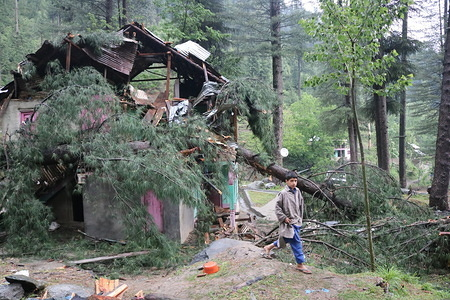 A kid walks past the damaged house.